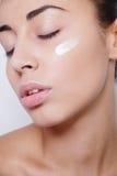 Bello trattamento crema cosmetico d'applicazione di modello sul suo bianco del fronte Fotografia Stock