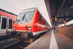Bello treno pendolare rosso al binario della ferrovia nella sera Fotografie Stock Libere da Diritti