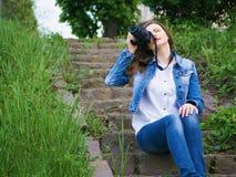 Bello turista della ragazza in un rivestimento del cotone che prende le foto con una macchina fotografica professionale sulle ban Immagine Stock