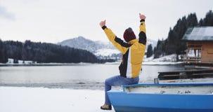 Bello turista di giorno di inverno che si siede sulla barca blu accanto della riva del lago ed ammirare il paesaggio della montag archivi video