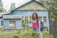 Bello turista rosso della donna dei capelli con lo zaino vicino alla casa nella foresta Immagini Stock
