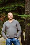 Bello, uomo brutale e gonfiato in un maglione grigio e jeans stan fotografia stock libera da diritti