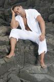 Bello uomo che si siede sulle rocce Immagini Stock