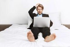 Bello uomo d'affari unshaved biondo che si trova a letto, lavorando al computer portatile, tenente mano sulla testa con colpito fotografia stock