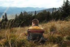 Bello uomo di viaggio alla moda che fa un'escursione nelle montagne su un BAC Immagine Stock Libera da Diritti