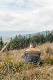 Bello uomo di viaggio alla moda che fa un'escursione nelle montagne su un BAC Fotografia Stock