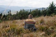 Bello uomo di viaggio alla moda che fa un'escursione nelle montagne su un BAC Immagini Stock