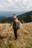 Bello uomo di viaggio alla moda che fa un'escursione nelle montagne su un BAC Immagini Stock Libere da Diritti