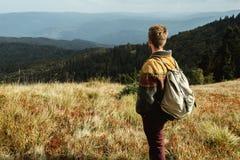 Bello uomo di viaggio alla moda che fa un'escursione nelle montagne su un BAC Fotografie Stock