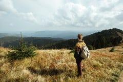 Bello uomo di viaggio alla moda che fa un'escursione nelle montagne su un BAC Fotografie Stock Libere da Diritti