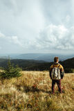 Bello uomo di viaggio alla moda che fa un'escursione nelle montagne su un BAC Immagine Stock