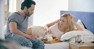 Bello uomo e donna che mangiano prima colazione con le brioche a letto Le coppie nella mattina di amore svegliano a casa in camer video d archivio