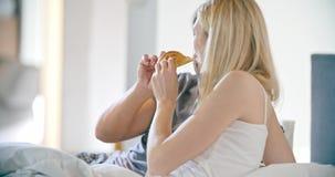 Bello uomo e donna che mangiano prima colazione con le brioche a letto Le coppie nella mattina di amore svegliano a casa in camer stock footage