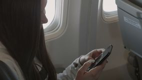 Bello uso della ragazza del telefono cellulare dentro l'aeroplano archivi video