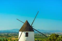 Bello vecchio mulino di vento bianco medievale in valle con i prati verdi degli alberi della vegetazione sul fondo del cielo blu  immagine stock libera da diritti