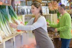 Bello venditore femminile sorridente che posa con i porri in supermercato fotografia stock libera da diritti