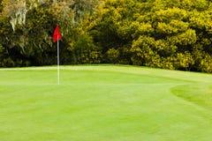 Bello verde di golf con la bandiera rossa Fotografia Stock