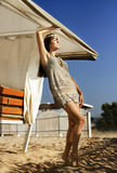 Bello vestito da short della ragazza che sta sulla sabbia sotto un ombrello fotografia stock libera da diritti