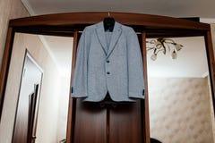 Bello vestito grigio del ` s dello sposo che appende sul guardaroba nella stanza immagini stock