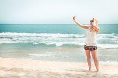 Bello viaggiatore solo della donna sulla spiaggia che prende il selfie dell'immagine sul telefono durante la vacanza di feste di  fotografia stock libera da diritti