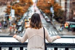 Bello viaggio della donna ed esaminare la via di New York con traffico di automobile e gli alberi gialli a tempo di autunno da pa immagine stock libera da diritti