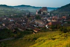 Bello villaggio del sassone di Transylvanian e chiesa fortificata alla luce solare di mattina Immagine Stock