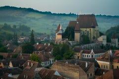 Bello villaggio del sassone di Transylvanian e chiesa fortificata alla luce solare di mattina Fotografia Stock