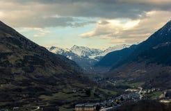 Bello villaggio situato in una valle circondata dalle montagne al tramonto fotografia stock