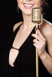 Bello vocalist della ragazza con il sorriso che tiene microp d'annata dorato immagine stock libera da diritti