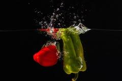 Bellpepper rojo y verde que cae en el agua Imagen de archivo