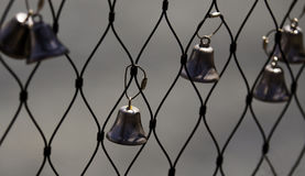 Bells attached to a waterfront fence Stock Images