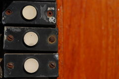 Bells on a door in a row. Three doorbells on a wooden background Royalty Free Stock Photo