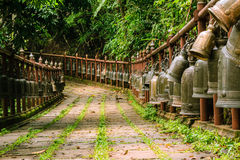 Bells hanging on rail along walking path. Stock Photos