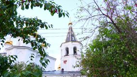 Bells ringing in the cathedral of the monastery. Golden domes and cross against the blue sky. Bells ringing in cathedral of monastery. Golden domes and cross stock video