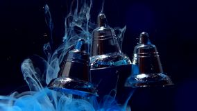Bells three shiny silver Christmass bells on a dark blue background. Christmas background.