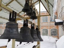 Bells of various sizes. A row of bells of several different sizes in the monastery courtyard on a winter day stock images