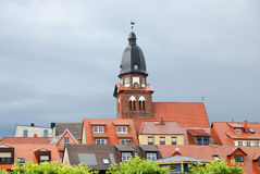Belltower of church. Belltower of city church over tiling roofs in Waren (Mueritz) in Germany, Europe royalty free stock photography