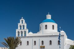 Belltower e cupola blu sulla chiesa greco ortodossa a OIA immagini stock libere da diritti