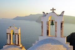 Belltowers at sunset in Oia. Two belltowers at sunset in Oia, Santorini royalty free stock photo