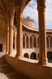Bellver Castle Colonnades. Columns and colonnades that encircle the courtyard of the circular Bellver Castle in Palma, Majorca with the top of one of the outer Stock Photo