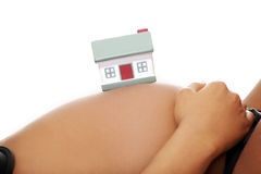 Belly in an advanced pregnancy with house model. Royalty Free Stock Photos