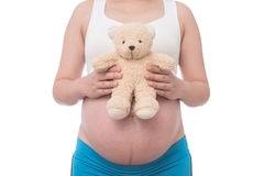 The belly asia pregnant woman holdind a teddy bear doll isolate Royalty Free Stock Photography
