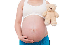 The belly asia pregnant woman holdind a teddy bear doll isolate Stock Photos