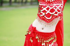 Belly close up belly dancer in red dress. Asian Chinese beauty belly dancer, dancing in forest, wear a red India stytle belly dance dress Royalty Free Stock Images