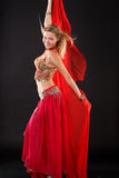 Belly dancer. Young blonde belly dancer in red stock image