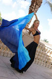 Belly dancer arching back. Pretty blonde belly dancer in black arching back while dancing outside on balcony Stock Photo