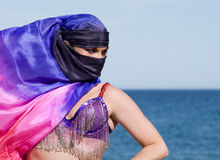 Belly Dancer on a Beach. On a sunny day with face covered Stock Images