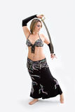 Belly dancer in black. Beautiful belly dancer in black outfit holding sword, isolated Royalty Free Stock Image