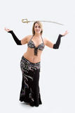 Belly dancer in black. Beautiful belly dancer in black outfit balancing sword, isolated Royalty Free Stock Photos