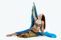 Belly dancer in blue. Beautiful belly dancer in blue outfit laying on floor, isolated Royalty Free Stock Photos